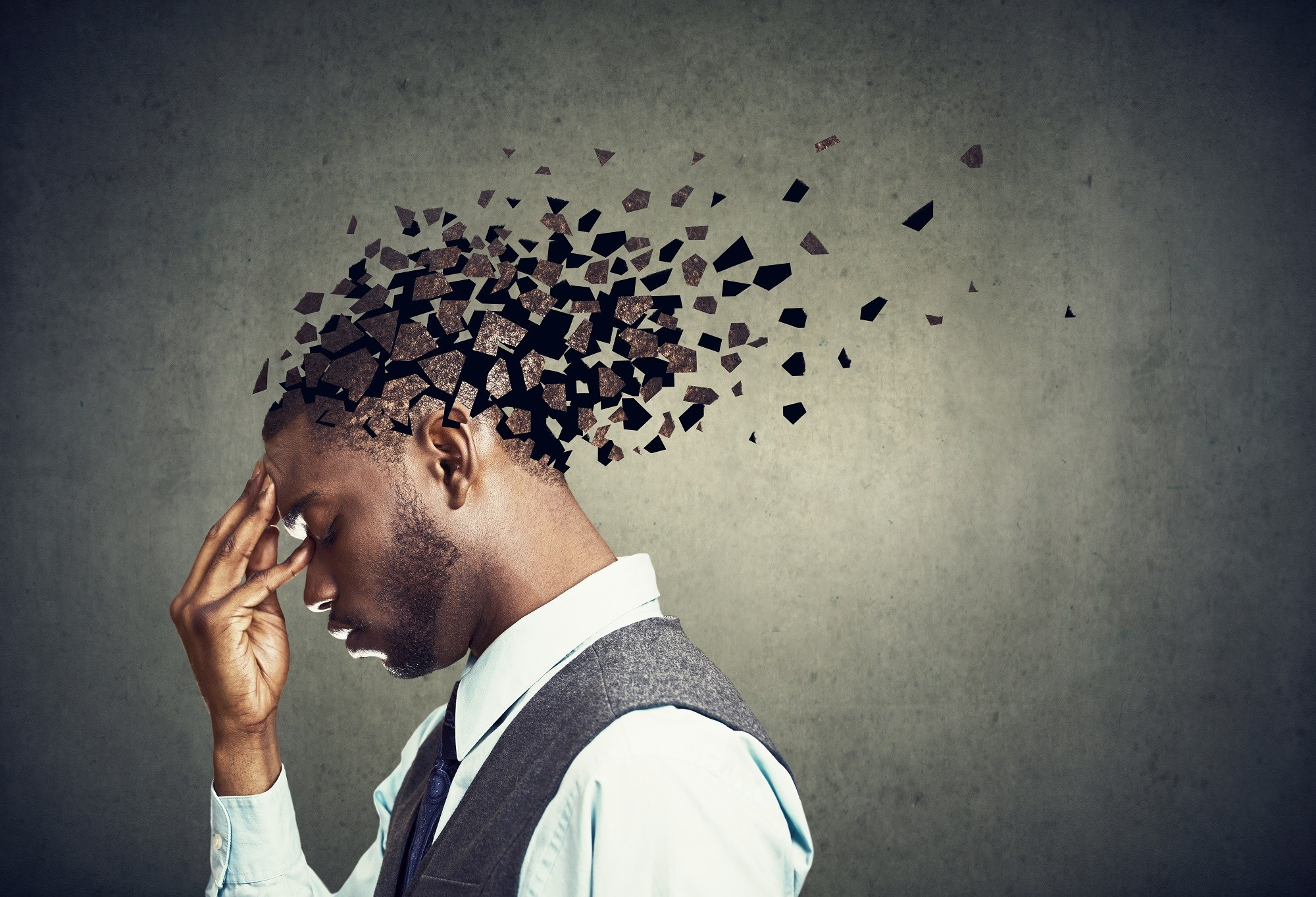 Side profile of a sad man losing parts of head as symbol of decreased mind function.